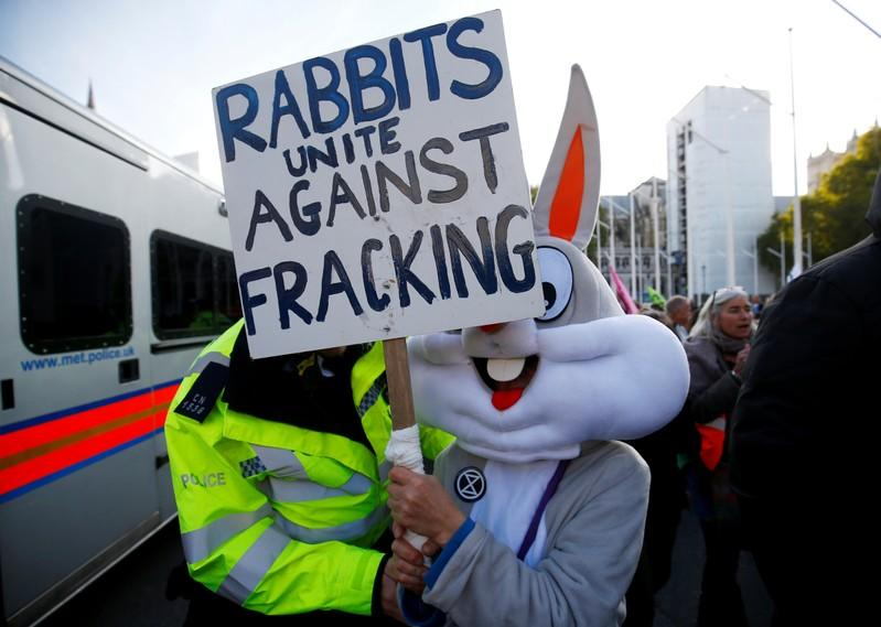 FILE PHOTO: A police officer moves a protester outside the Houses of Parliament during a demonstration against fracking, in London