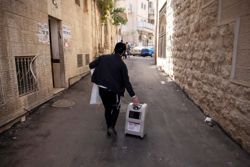 An ultra-Orthodox Jewish volunteer from Chasdei Amram, which provides home relief to people affected by the coronavirus coronavirus disease (COVID-19), carries a home oxygen concentrator as he makes his way in Jerusalem