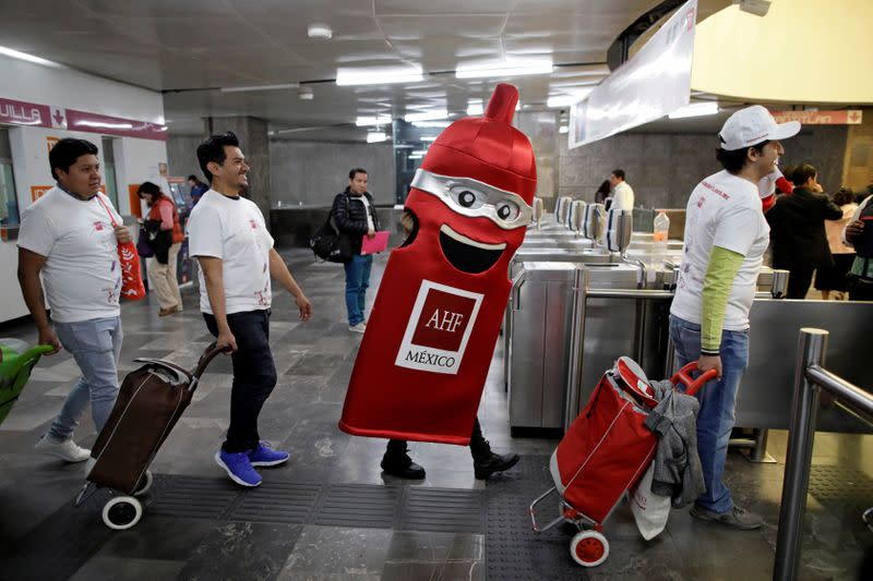 Members of an organization enter a metro station during an event organized by AIDS Healthcare Foundation for the International Condom Day, in Mexico City