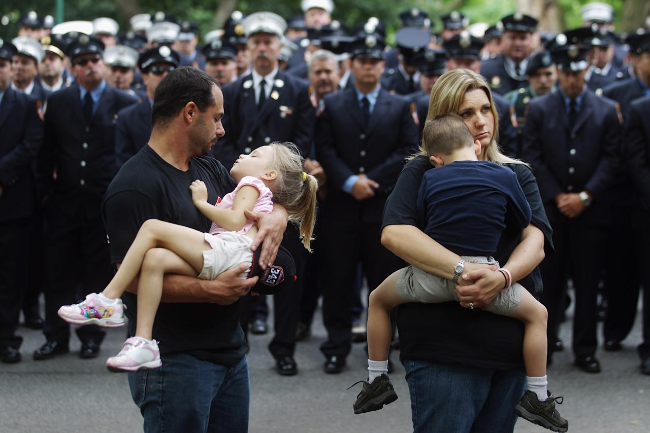 NEW YORK, NY - SEPTEMBER 11:  Martin County, Florida Fire Rescue firefighter Sean McCallister (L) holds his daughter Caitlyn while wife Julia (R) holds their son Sean at a memorial service for firefighters killed on 9/11 at the Firemen's Monument at Riverside Park on Septemnber 11, 2011 in New York City. Firefighters from around the world have converged on New York to take part in the anniversary services. New York City and the nation are commemorating the tenth anniversary of the terrorist attacks which resulted in the deaths of nearly 3,000 people after two hijacked planes crashed into the World Trade Center, one into the Pentagon in Arlington, Virginia and one crash landed in Shanksville, Pennsylvania.  (Photo by Mario Tama/Getty Images)