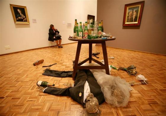 """A security guard at the San Carlos museum in Mexico City sits in her chair behind a piece by British artist Damien Hirst titled """"Adam and Eve under the table"""" between two 16th century paintings October 6, 2006."""