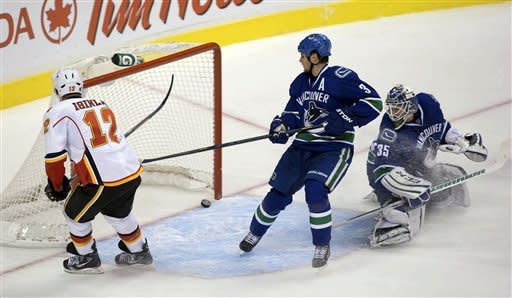 From left, Calgary Flames' Jarome Iginla, Vancouver Canucks' Kevin Bieksa and goalie Cory Schneider watch as the puck enters the net off the stick of Flames' Alex Tanguay, not pictured, for a goal during the second period of their NHL hockey game, Wednesday, Jan. 23, 2013, in Vancouver, British Columbia. (AP Photo/The Canadian Press, Darryl Dyck)