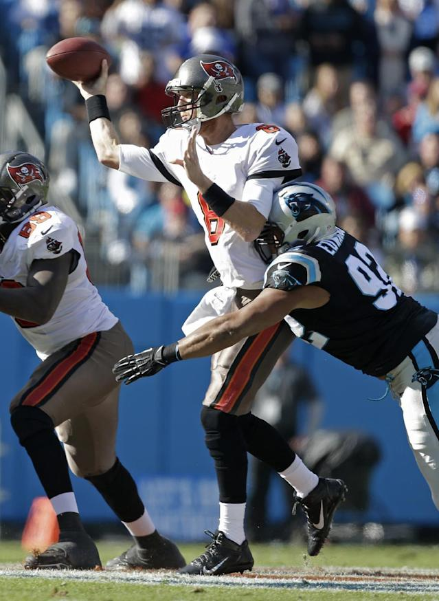 Tampa Bay Buccaneers' Mike Glennon (8) throws a pass under pressure from Carolina Panthers' Dwan Edwards (92) in the first half of an NFL football game in Charlotte, N.C., Sunday, Dec. 1, 2013. (AP Photo/Bob Leverone)