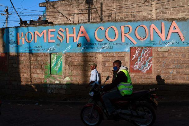 PHOTO: A motorcycle taxi rider cruises past a painted wall with the Swahili slogan that translates to 'stop corona,' in Nairobi, Kenya, April 8, 2020. (SOPA Images/LightRocket via Getty Images)