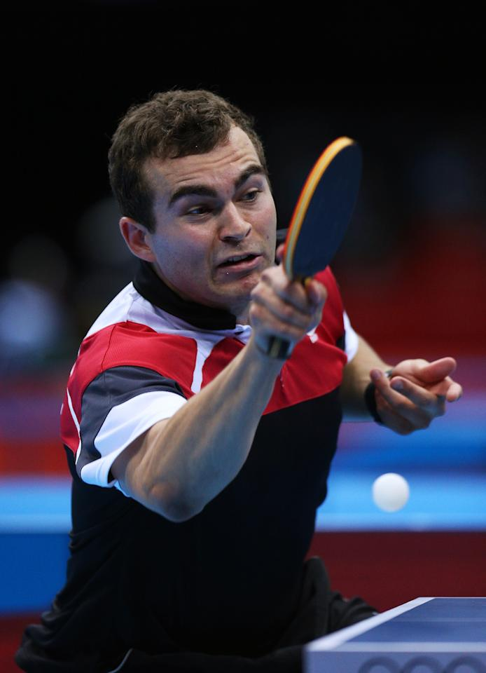 LONDON, ENGLAND - JULY 28:  Pierre-Luc Hinse of Canada plays a forehand against Matiss Burgis of Latvia during their Men's Singles Table Tennis match on Day 1 of the London 2012 Olympic Games at ExCeL on July 28, 2012 in London, England.  (Photo by Feng Li/Getty Images)