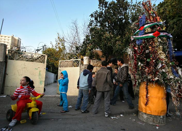 """Palestinian children gather around a Christmas Tree during a ceremony in the East Jerusalem neighborhood of Sheikh Jarrah on Dec. 23, 2009.<span class=""""copyright"""">Dan Balilty—AP</span>"""