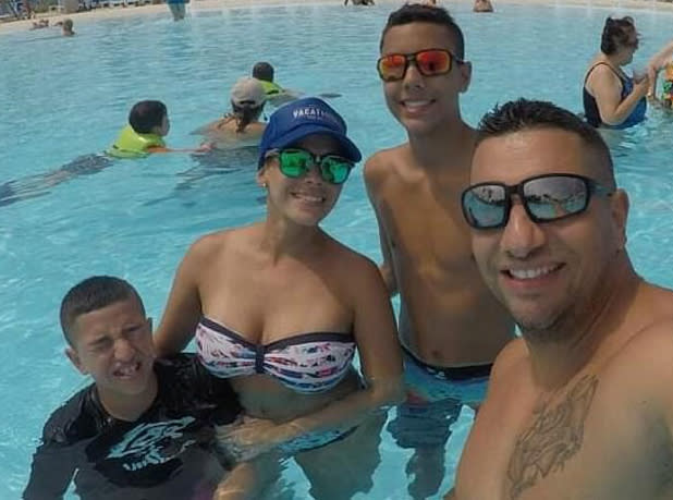 Ezequiel Almodovar, 39, Marielis Soto, 38, Ezequiel Almodovar, 16, and 12-year-old Gabriel Almodovar are all pictured in a swimming pool.