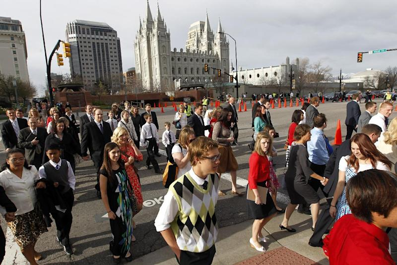 FILE - This April 6, 2013, file photo, shows the Salt Lake Temple as people walk to the Conference Center before the start of the 183rd Annual General Conference of The Church of Jesus Christ of Latter-day Saints, in Salt Lake City. More than 100,000 Latter-day Saints are expected in Salt Lake City this weekend for the church's biannual general conference. Leaders of The Church of Jesus Christ of Latter-day Saints give carefully crafted speeches aimed at providing members with guidance and inspiration in five sessions that span Saturday and Sunday. They also make announcements about church statistics, new temples or initiatives. In addition to those filling up the 21,000-seat conference center during the sessions, thousands more listen or watch around the world in 95 languages on television, radio, satellite and Internet broadcasts. A Mormon's women group pushing the church to allow women in the priesthood plans to demonstrate outside an all-male meeting Saturday. The church has asked them to reconsider, and barred media from going on church property during the demonstration. (AP Photo/Rick Bowmer, File)