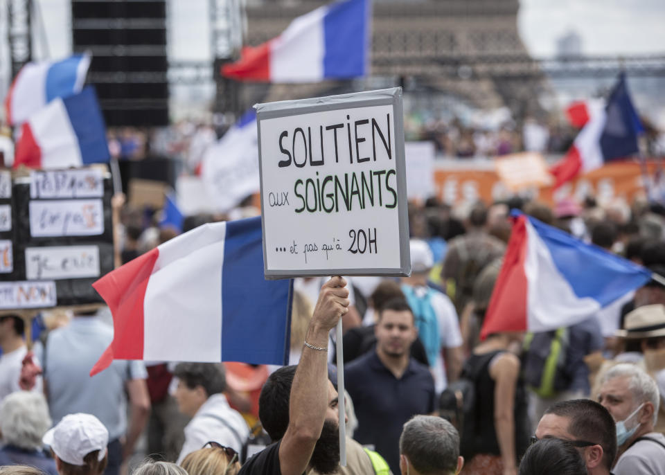 """A banner that reads: """"Support to health workers and not only at 8pm"""", is held up during a demonstration in Paris, France, Saturday 24, 2021, against the COVID-19 pass which grants vaccinated individuals greater ease of access to venues (AP Photo/Rafael Yaghobzadeh)"""
