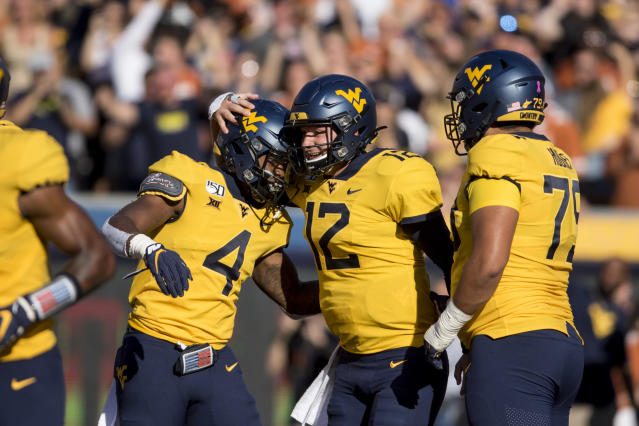 West Virginia quarterback Austin Kendall (12) and West Virginia running back Leddie Brown (4) celebrate after Kendall ran for a touchdown during the first half of an NCAA college football game Saturday, Oct. 5, 2019, in Morgantown, W.Va. (AP Photo/Raymond Thompson)