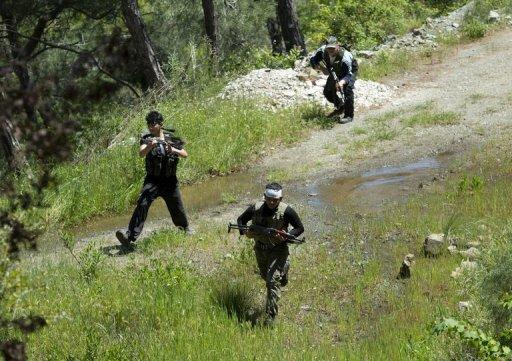 Rebel fighters from the al-Ezz bin Abdul Salam Brigade attend a training session at an undisclosed location near the al-Turkman mountains, in Syria's northern Latakia province, on April 24, 2013. Lebanon's Shiite Hezbollah movement came under increasing pressure over accusations it is backing regime troops in Syria, as a rebel leader warned of the risk of sparking a sectarian war