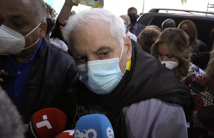 Panama's former President Ricardo Martinelli arrives to court, surrounded by press, for the start of his trial in Panama City, Wednesday, July 21, 2021. Martinelli faces trial for alleged eavesdropping on political rivals and journalists during his administration, the same case for which he was acquitted in 2018. (AP Photo/Arnulfo Franco)