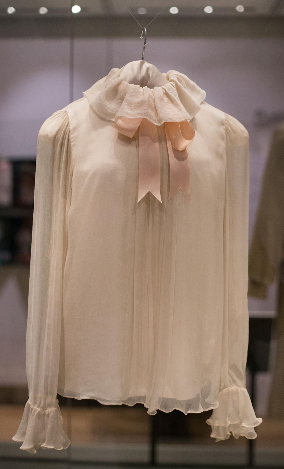 """A chiffon blouse by the designer Emanuel, and worn by Princess Diana, at her first official portrait by Lord Snowdon, consequently published in Vogue in February 1981, is pictured during a press preview of the forthcoming exhibition entitled """"Diana: Her Fashion Story"""", at Kensington Palace in London on February 22, 2017. Glittering gowns, elegant suits and bold mini-dresses worn by the late Princess Diana will go on show from Friday on the 20th anniversary of her death in a unique exhibition charting her style reign. """"Diana: Her Fashion Story"""" follows her evolution from the demure outfits of her first public appearances to the glamourous gowns of her later life and is being hosted in Kensington Palace, her London residence. / AFP / Daniel LEAL-OLIVAS        (Photo credit should read DANIEL LEAL-OLIVAS/AFP via Getty Images)"""