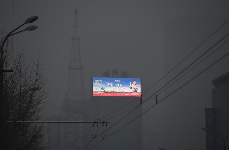 A scene of blue skies over the Temple of Heaven is seen on an electronic billboard through pollution in Beijing on November 27, 2015 (AFP Photo/Greg Baker)