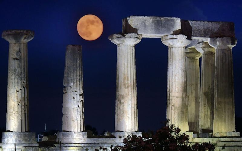 June's full moon, known as the Strawberry Moon, rises above the Apollo Temple in ancient Corinth, on June 17, 2019 - AFP