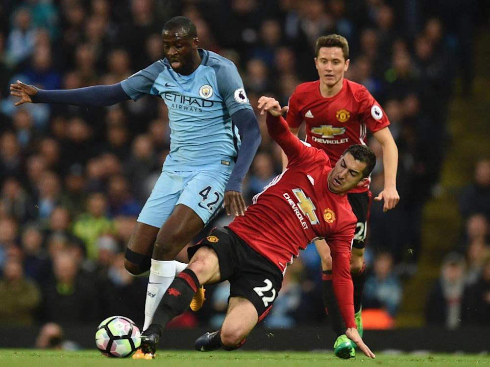 Toure attempts to get away from Mkhitaryan (AFP/Getty Images)