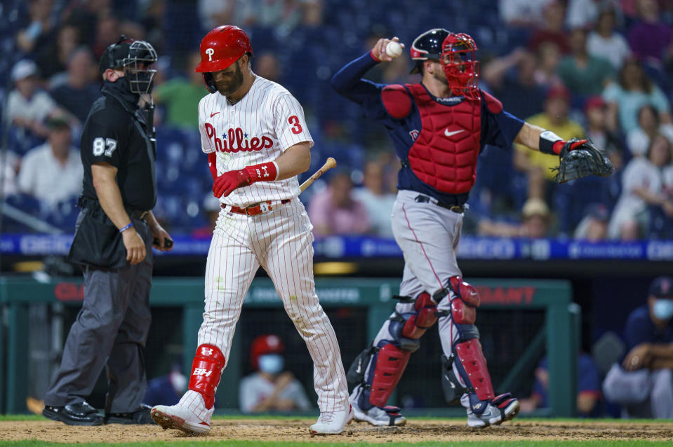 Philadelphia Phillies' Bryce Harper, center, walks back to the dugout after striking out during the seventh inning of the team's baseball game against the Boston Red Sox, Saturday, May 22, 2021, in Philadelphia. The Red Sox won 4-3. (AP Photo/Chris Szagola)
