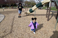 Michael Diaz-Rivera plays with his 2-year-old daughter Aria at a Denver park on Friday, April 23, 2021. Diaz-Rivera was pulled over in Colorado Springs, Colorado in 2006, and officers found two bags of marijuana in his car. After he was convicted of felony drug possession, he struggled to find housing, ran into hurdles while applying for federal student aid and was denied jobs. Now an elementary school teacher, he sees his future in a pot delivery business made possible by Colorado's marijuana social equity program, which is aimed at correcting past wrongs from the war on drugs. Diaz-Rivera says he hopes his business will allow him to pass on to his children generational wealth that he did not have growing up. (AP Photo/Thomas Peipert)