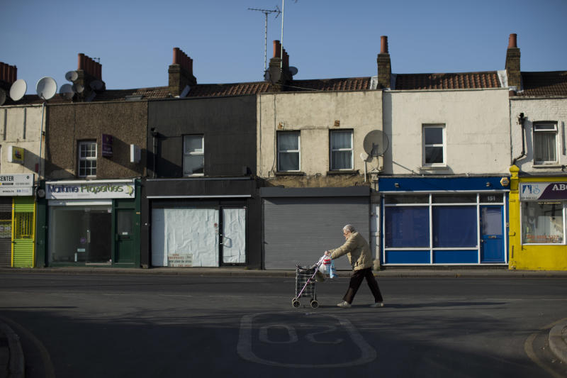 """Britain High Street Lows** An elderly lady walks with a wheelie shopping bag past four closed shops on Trafalgar Road in Greenwich, London, Tuesday, March 5, 2013.  The small shopkeepers in Greenwich are running out of time.  In the London borough that gave its name to Greenwich Mean Time, businesses like Lorraine Turton's are in danger of being relegated to history _ the victims of online shopping, changing tastes and, increasingly, the protracted recession. Her Internet cafe on Trafalgar Road is a rare hive of activity on a """"high street"""" _ the British name for a town's main business district.  (AP Photo/Matt Dunham)"""