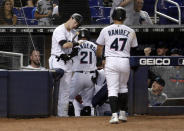 Miami Marlins' Brian Anderson, left, greets Curtis Granderson (21) and Harold Ramirez (47) after they scored during the second inning of a baseball game against the Arizona Diamondbacks, Monday, July 29, 2019, in Miami. (AP Photo/Lynne Sladky)