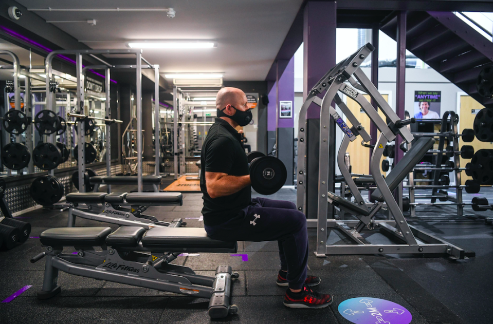 A man wears a face mask as he works out in a gym. (SWNS)