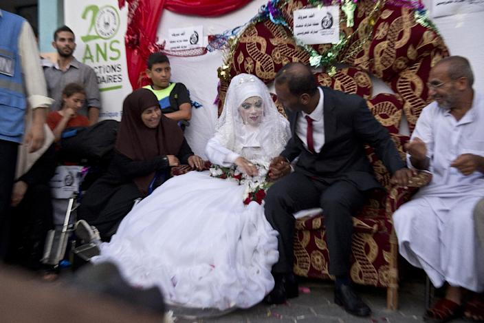Omar Abu Namar, 30, (R) and his wife Heba Fayad, 23, (L) attend their wedding ceremony at a UN school school in Gaza City's Shati refugee camp on August 13, 2014 (AFP Photo/Roberto Schmidt)
