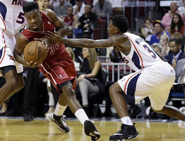 Miami Heat's Norris Cole (30) drives to the basket as Atlanta Hawks' Louis Williams (3) defends in the first half of an NBA basketball game, Monday, Dec. 23, 2013, in Miami. (AP Photo/Lynne Sladky)