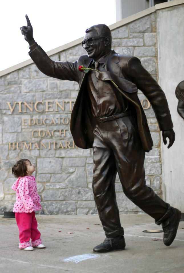 FILE - Sabine Briggs, 2, looks up at a statue of Joe Paterno outside Beaver Stadium on Penn State's campus, in this Nov. 11, 2011 file photo taken in State College, Pa. Police and construction workers have barricaded both sides of street and the sidewalks near the Joe Paterno statue at Penn State University early Sunday July 22, 2012. A chain-link fence has been erected around the perimeter surrounding the statue. (AP Photo/Matt Rourke, File)
