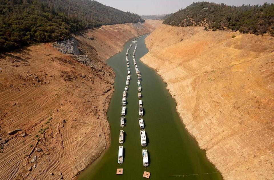 Houseboats sit in a narrow section of water in a depleted Lake Oroville in California, which is currently at 23% of its capacity, suffering from extreme levels of drought (AFP via Getty Images)