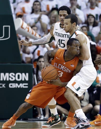 Clemson Adonis Filer (3) tries to get around Miami's Trey McKinney Jones (4) and Julian Gamble (45) during the first half of a NCAA college basketball game in Coral Gables, Fla., Saturday, March 9, 2013. (AP Photo/J Pat Carter)