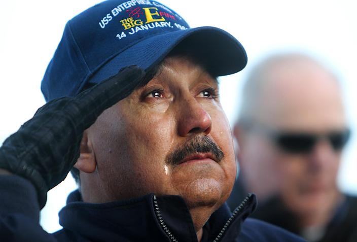 """USS Enterprise alumnus Jimmy Gonzales struggles to hold back tears during a ceremony to honor those who were killed in the Jan. 14, 1969 fire, on the ships flight deck at Naval Station Norfolk, Va. on Friday, Nov. 30, 2012, Gonzales, who lives near Dallas, set foot on The Big E for the first time since he was an 18 year-old Seaman Apprentice who helped care for the wounded and dying. """"I hadn't even made it to Vietnam yet,"""" Gonzales remembers, """"and I had already seen more than most."""" Thousands of alumni will visit the ship this weekend during the carrier's inactivation ceremony events at Naval Station Norfolk. (AP Photo/The Virginian-Pilot, Stephen M. Katz) MAGS OUT"""