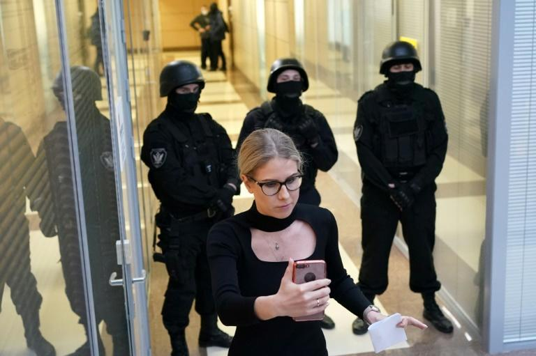 Opposition politician Lyubov Sobol uses her phone near law enforcement agents in the building housing Alexei Navalny's Anti-Corruption Foundation office