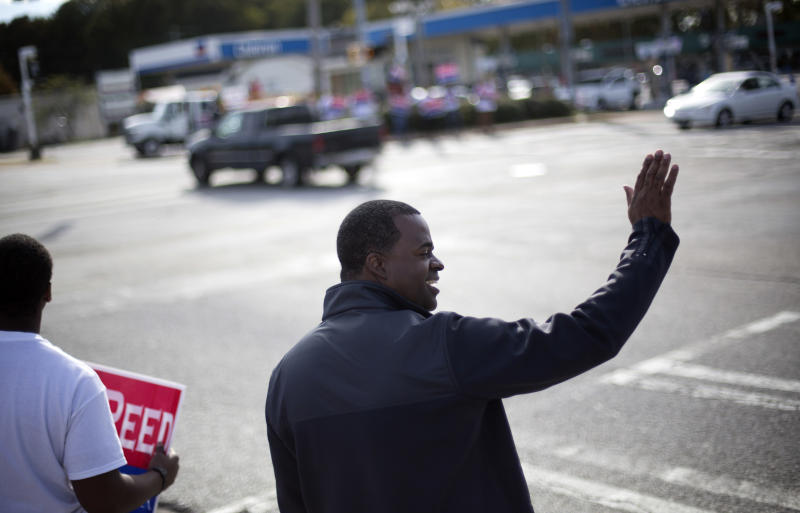 Atlanta Mayor Kasim Reed waves to passing motorists as he campaigns at an intersection in west Atlanta, Tuesday, Nov. 5, 2013. Voters head to the polls Tuesday to decide whether Mayor Reed has earned a second term. Reed faces three challengers. (AP Photo/David Goldman)