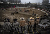 Horseback riders take part in a traditional rodeo competition, a centerpiece of the country's Independence Day celebrations, at an arena empty of spectators due to the restrictions related to the COVID-19 pandemic, in Melipilla, Chile, on Saturday, Sept. 18, 2021. (AP Photo/Esteban Felix)