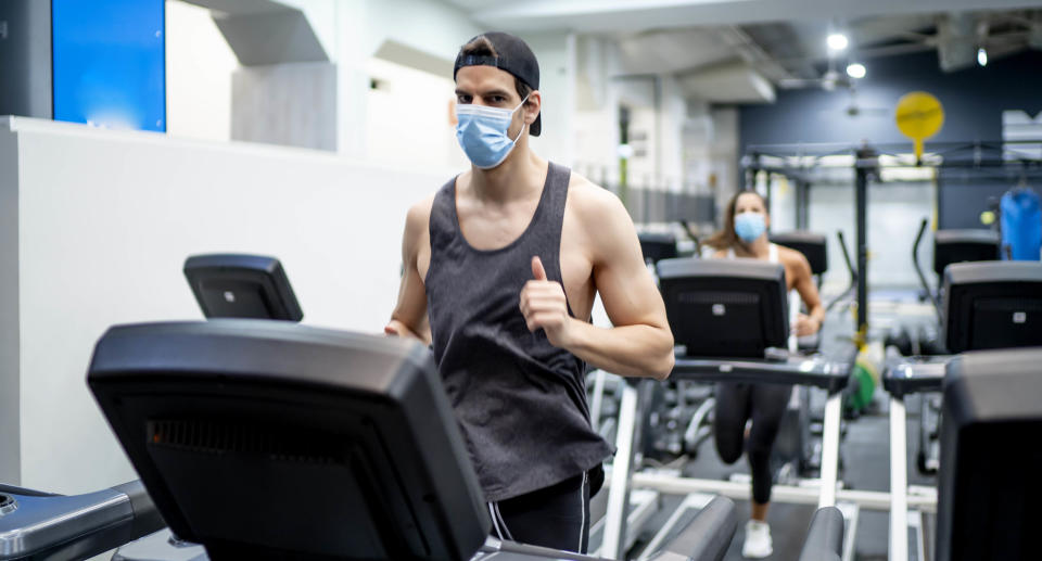 Several young people running on treadmill in gym wearing face mask. Source: Getty Images
