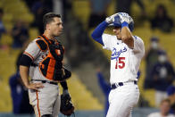 Los Angeles Dodgers' Austin Barnes grabs his helmet as he reaches home plate past San Francisco Giants catcher Buster Posey after Barnes three-run home run during the ninth inning of a baseball game Friday, May 28, 2021, in Los Angeles. (AP Photo/Marcio Jose Sanchez)