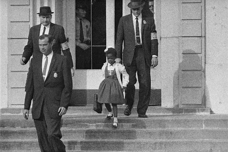 FILE - In this Nov. 1960 file photo, U.S. Deputy Marshals escort six-year-old Ruby Bridges from William Frantz Elementary School in New Orleans, La. The first grader was the only black child enrolled in the school, where parents of white students were boycotting the court-ordered integration law and were taking their children out of school. Ruby Bridges will be one of the presenting authors at this weekend's New Orleans Children's Book Festival, an event Bridges helped launch in 2010. (AP Photo, file)