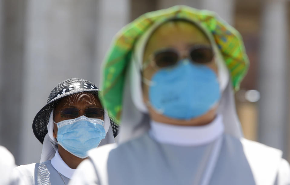 Nuns wearing protective masks attend the Angelus prayer celebrated by Pope Francis from his studio window overlooking St. Peter's Square at the Vatican, Sunday, July 5, 2020. (AP Photo/Riccardo De Luca)