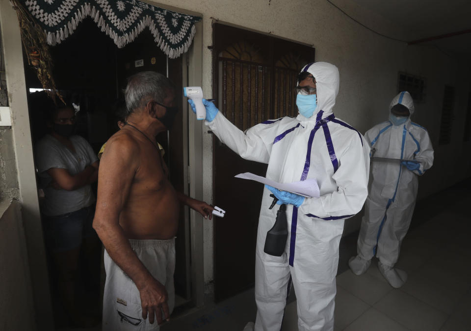 """A health worker checks the temperature of a man during a free medical checkup at residential building in Mumbai, India, Thursday, July 2, 2020. Indian Prime Minister Narendra Modi said in a live address Tuesday that the country's coronavirus death rate is under control, but that the country is at a """"critical juncture."""" But since the lockdown was lifted, the caseload has shot up, making India the world's fourth-worst affected country. (AP Photo/Rafiq Maqbool)"""