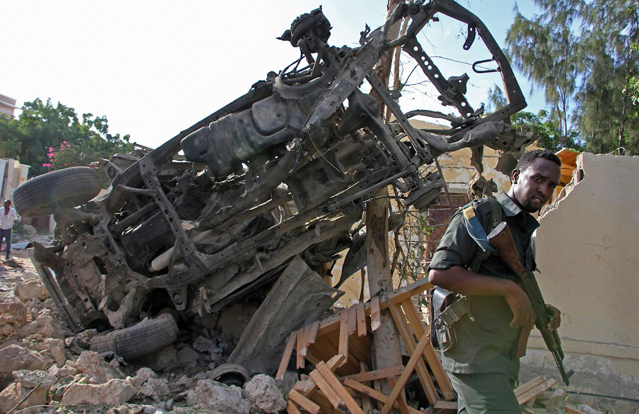 <p>A Somali soldier stands near the wreckage from a car bomb blast and gun battle targeting a restaurant in Mogadishu, Somalia, Thursday, June 15, 2017. (Photo: Farah Abdi Warsameh/AP) </p>