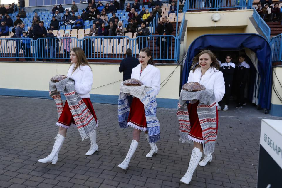 In this photo taken on Friday, March 27, 2020, women dressed in Belarusian national clothes carry traditional bread to greet players prior to the Belarus Championship soccer match between Torpedo-BelAZ Zhodino and Belshina Bobruisk in the town of Zhodino, Belarus. Longtime Belarus President Alexander Lukashenko is proudly keeping soccer and hockey arenas open even though most sports around the world have shut down because of the coronavirus pandemic. The new coronavirus causes mild or moderate symptoms for most people, but for some, especially older adults and people with existing health problems, it can cause more severe illness or death. (AP Photo/Sergei Grits)