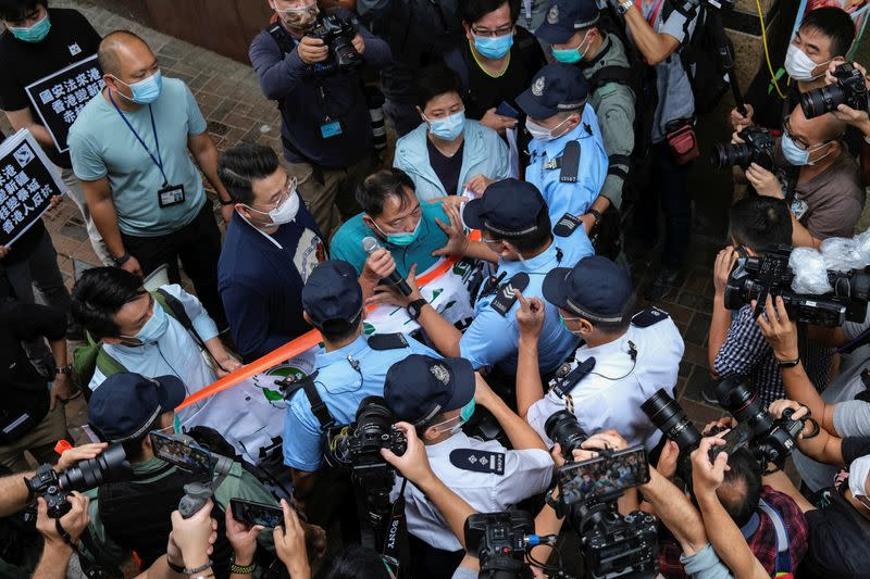 Pro-democracy lawmaker Wu Chi-wai scuffles with police during a march against new security laws, near China's Liaison Office, in Hong Kong