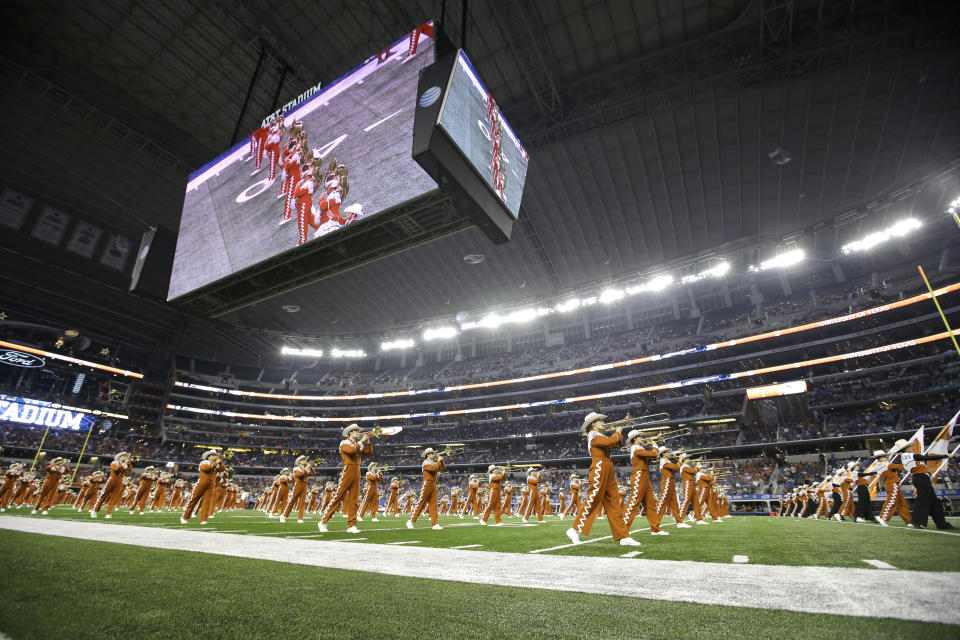 The Texas Longhorns marching band performs on the field at halftime of an NCAA college football game against UCLA, Saturday, Sept. 13, 2014, in Arlington, Texas. (AP Photo/Tony Gutierrez)