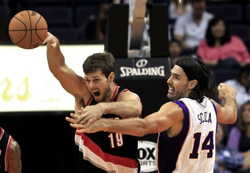 Portland Trail Blazers' Joel Freeland (19), of England, gets a pass off as Phoenix Suns' Luis Scola (14), of Argentina, defends during the first half of an NBA preseason basketball game Friday, Oct. 12, 2012, in Phoenix. (AP Photo/Ross D. Franklin)