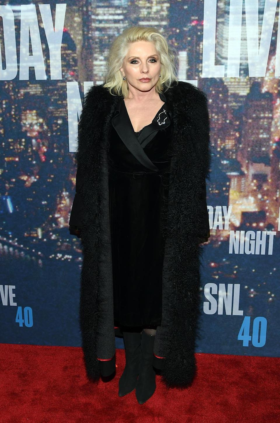 Blondie brings it like only an icon can in a long black fur coat, velvet dress, and booties.