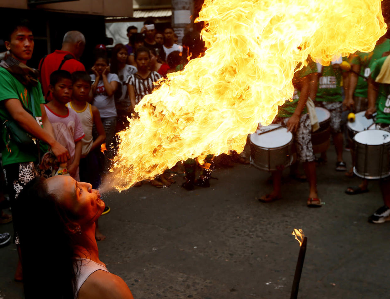 A fire-eater performs on the street during Chinese New Year celebrations, Saturday, Jan. 28, 2017, in the Chinatown area of Manila, Philippines. Chinese around the world are celebrating this year's Year of the Rooster according to the Chinese zodiac calendar. (AP Photo/Bullit Marquez)