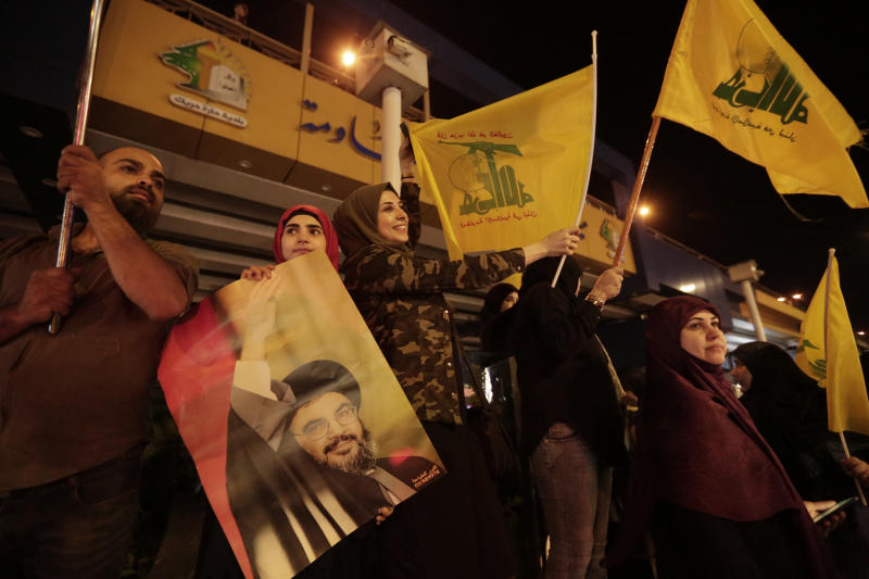 FILE - In this Oct. 25, 2019 file photo, supporters of Hezbollah leader Sayyed Hassan Nasrallah hold his pictures and waves Hezbollah flags in the southern suburb of Beirut, Lebanon. Iranian-backed Hezbollah built a reputation among supporters in Lebanon as a champion of the poor and a defender of the country against Israel's much more powerful military. Lebanon's protests have shown unusual overt anger at the country's powerhouse, Hezbollah. (AP Photo/Hassan Ammar, File)