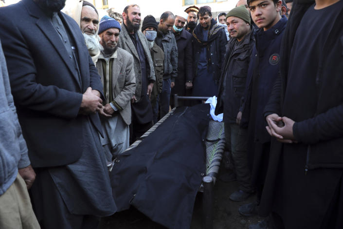 People gather around the body of man killed after a roadside bomb attack in Kabul, Afghanistan, Tuesday, Dec. 22, 2020. A roadside bomb tore through a vehicle in the Afghan capital of Kabul Tuesday, killing multiple people, police said. (AP Photo/Rahmat Gul)