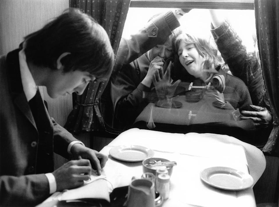 UNSPECIFIED - JANUARY 01:  Photo of BEATLES and George HARRISON; George Harrison on a train during the filming of a 'Hard Day's Night', with adoring fans outside looking through the window -  (Photo by Max Scheler - K & K/Redferns)