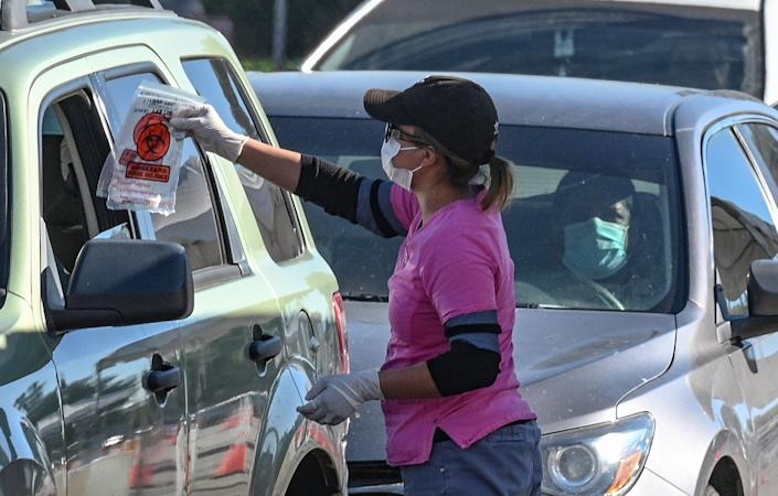 A COVID-19 testing site staff member gives a self-administered test kit to a person in their car at a drive-up testing site in Los Angeles, California, November 17, 2020. As coronavirus cases spike across California and the country officials are raising the alarm and admonishing people to avoid large indoor gatherings during the Thanksgiving holiday. (Robyn Beck /AFP via Getty Images/TNS)